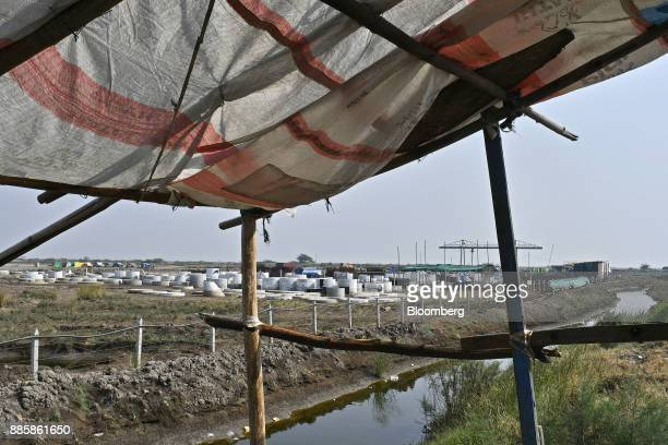 Building material sits at the project site for a 920squarekilometer industrial area located on the DelhiMumbai Industrial Corridor near the village...