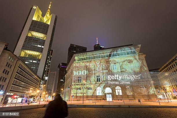 A building of the German bank 'Deutsche Bank' is illuminated with former German banknotes 'Deutsche Mark' on March 12 2016 in Frankfurt am Main...