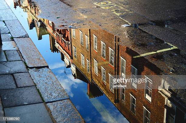 building reflected in roadside puddle
