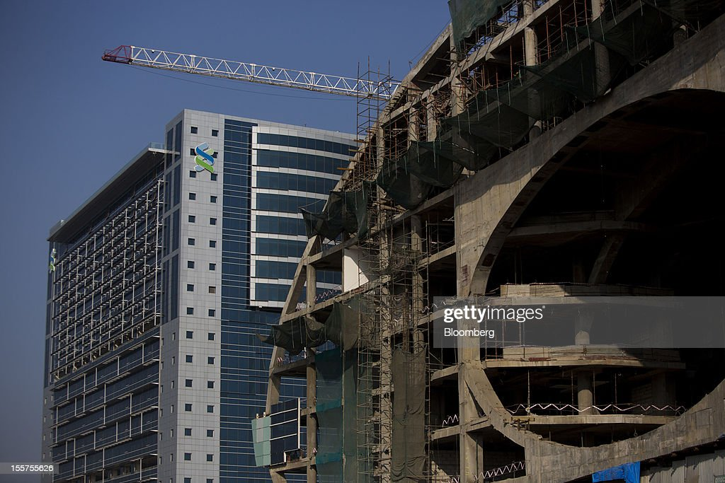 A building stands under construction next to the Standard Chartered Plc building in the Bandra Kurla Complex in Mumbai, India, on Tuesday, Nov. 6, 2012. Reserve Bank of India Governor Duvvuri Subbarao lowered the RBI's forecast for India's gross domestic product growth in the year through March to 5.8 percent, the slowest in almost a decade, from 6.5 percent. Photographer: Brent Lewin/Bloomberg via Getty Images