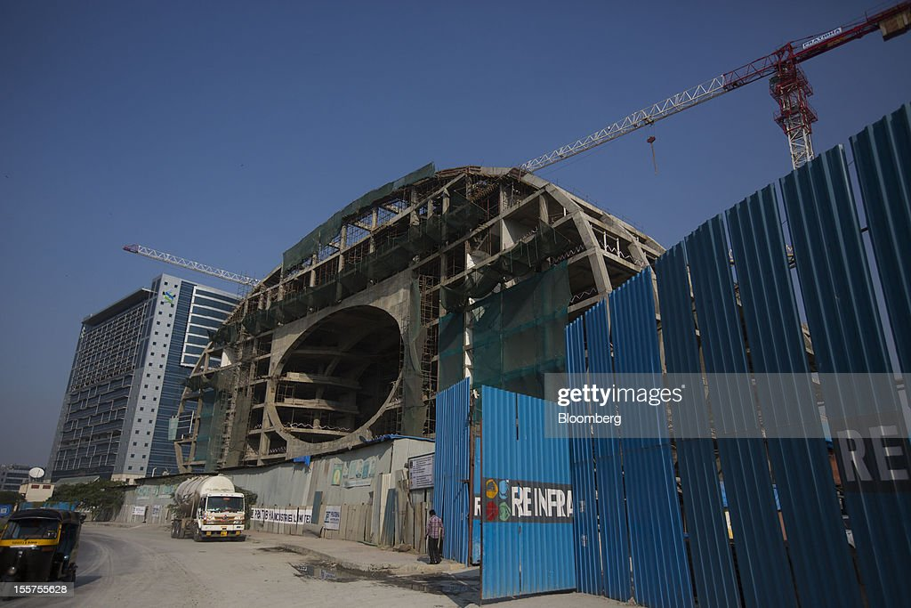 A building stands under construction next to the Standard Chartered Plc building, left, in the Bandra Kurla Complex in Mumbai, India, on Tuesday, Nov. 6, 2012. Reserve Bank of India Governor Duvvuri Subbarao lowered the RBI's forecast for India's gross domestic product growth in the year through March to 5.8 percent, the slowest in almost a decade, from 6.5 percent. Photographer: Brent Lewin/Bloomberg via Getty Images