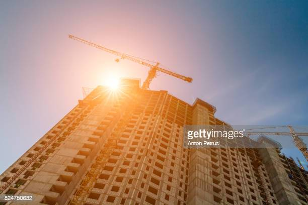 Building under construction with a crane against the sunset
