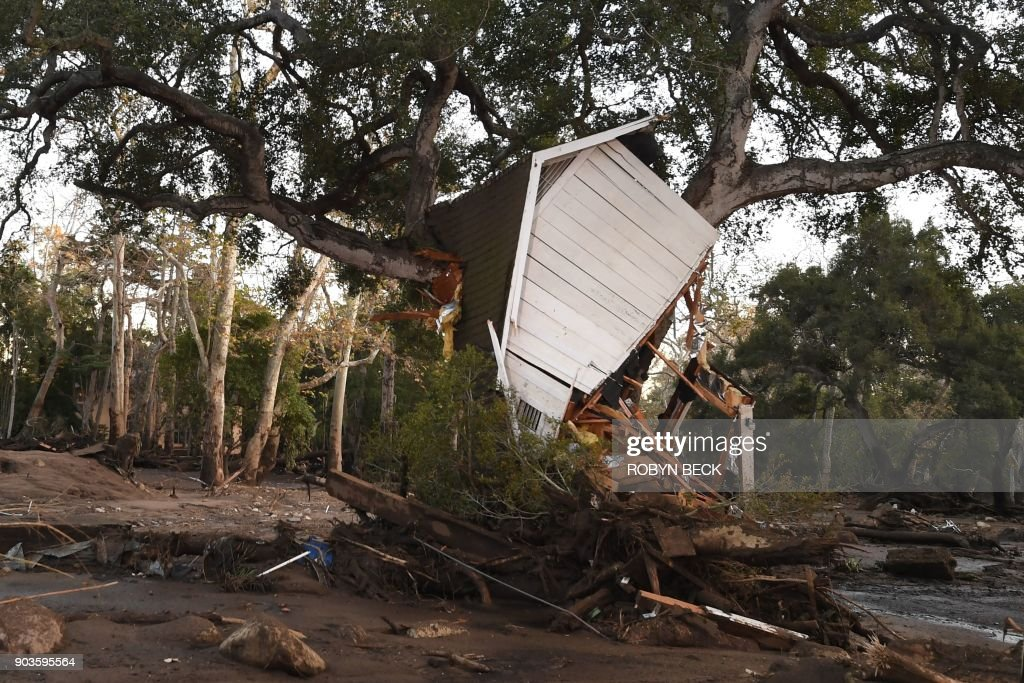 A building uprooted by a massive mudslide is lodgedin a tree in Montecito, California, January 10, 2018. Rescuers used dogs and helicopters to search for victims of powerful mudslides which left at least 15 people dead in a southern California community that is also home to major celebrities including Oprah Winfrey. Heavy rains sent rivers of waist-high mud and debris flowing from the hills into Montecito and other towns in Santa Barbara County northwest of Los Angeles, which are still recovering from last month's ferocious wildfires. PHOTO / Robyn Beck