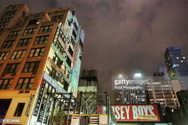 Building with mural along West 44th Street in Midtown Manhattan at night, New York City, USA