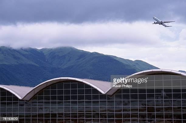 building with plane - hong kong international airport stock photos and pictures