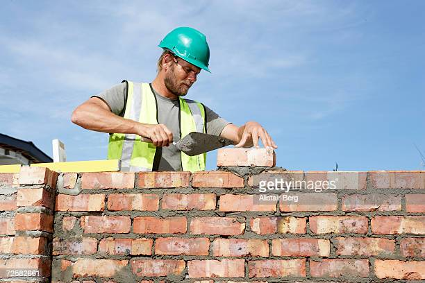 Building worker laying bricks