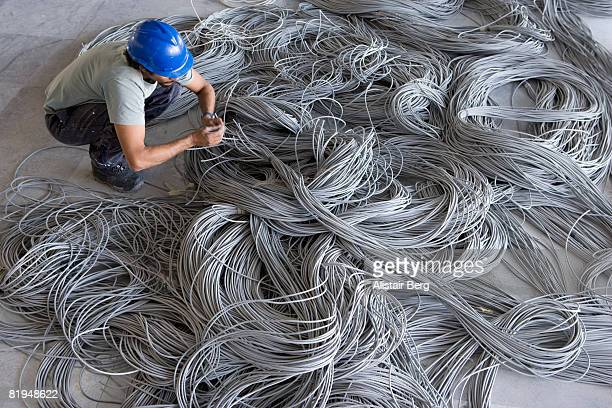 building worker with pile of network cables - cable stock pictures, royalty-free photos & images
