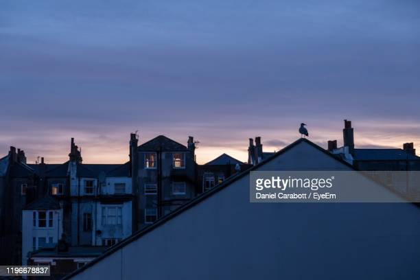 buildings against cloudy sky at dusk - hove stock pictures, royalty-free photos & images