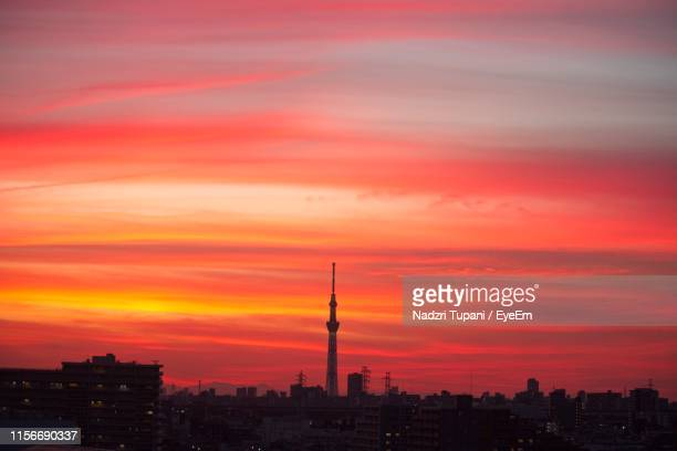 buildings against cloudy sky during sunset - ロマンチックな空 ストックフォトと画像