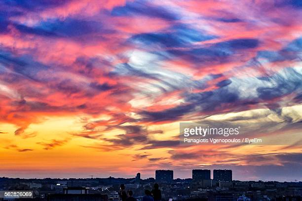 buildings against cloudy sky during sunset - vgenopoulos stock pictures, royalty-free photos & images