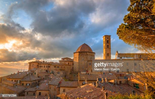 buildings against cloudy sky during sunset - volterra stock photos and pictures