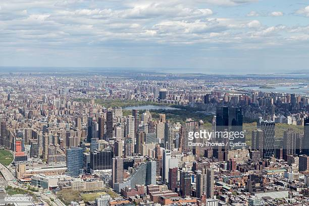 buildings against sky at central park in city - central park reservoir stock pictures, royalty-free photos & images