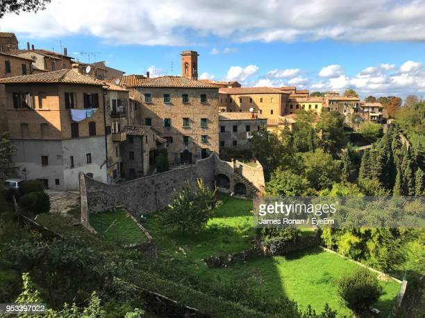 buildings against sky in city - volterra stock photos and pictures