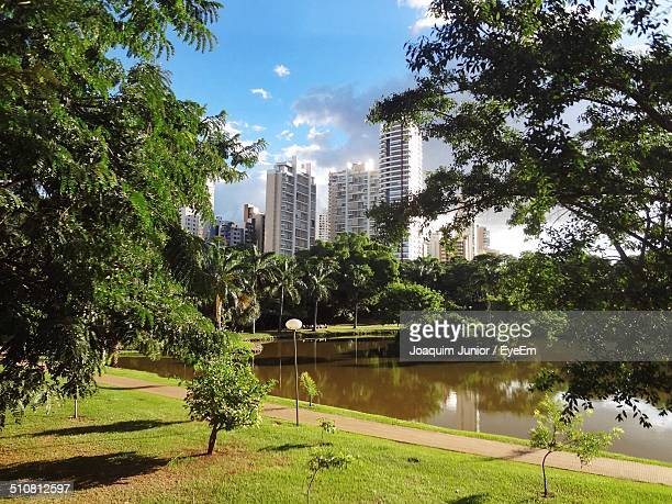 buildings against the sky with lake in foreground - goiania stock pictures, royalty-free photos & images