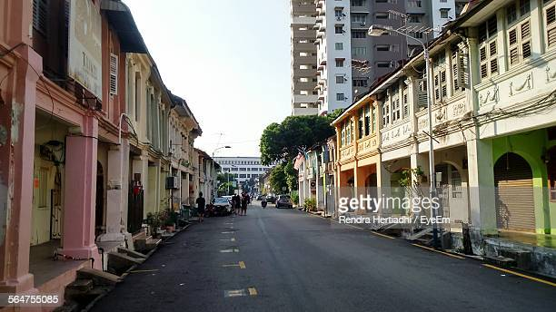buildings along road against sky - george town penang stock photos and pictures