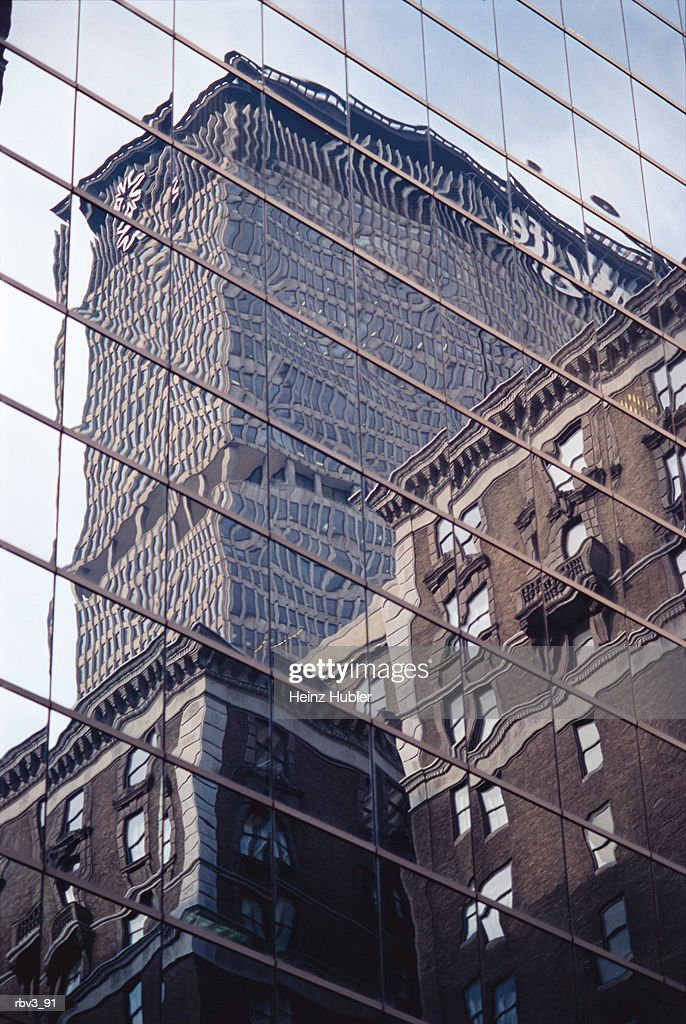buildings and a skyscraper are reflected in the glass windows of a large building : Foto de stock