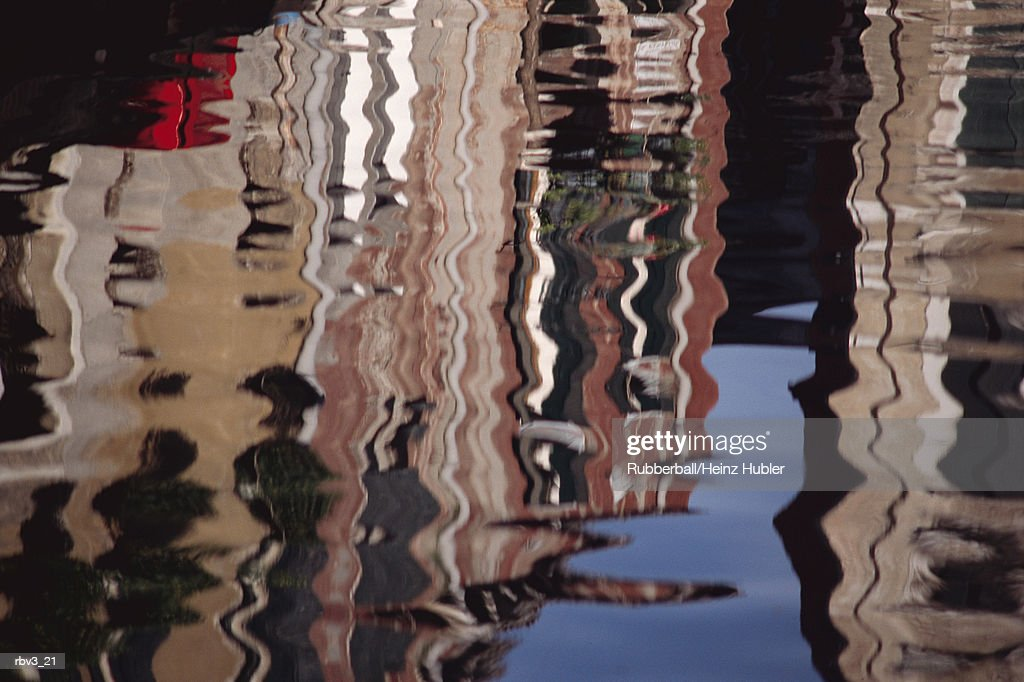 buildings and blue sky can be seen in a canal reflection : Foto de stock