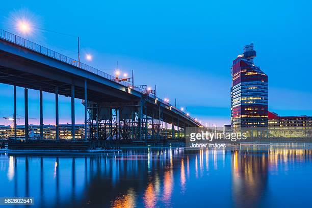Buildings and bridge reflecting in water