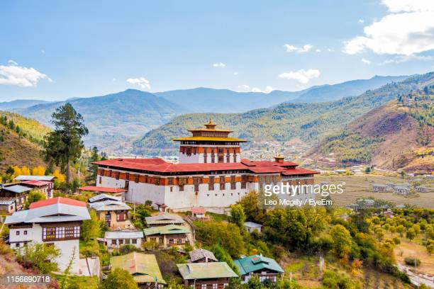 buildings and mountains against sky - paro stock pictures, royalty-free photos & images
