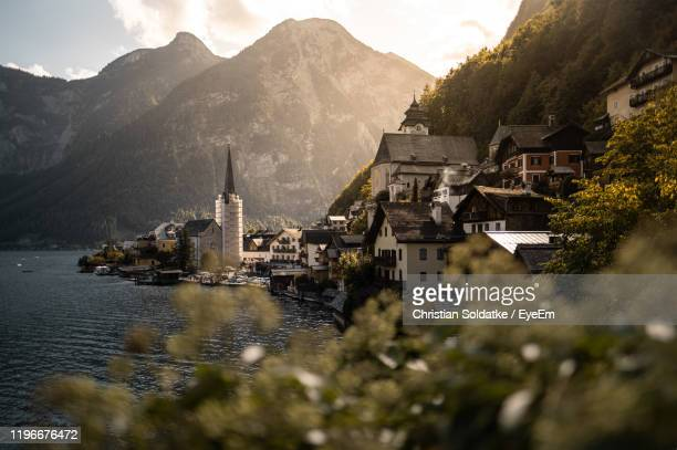 buildings and mountains by lake in city - christian soldatke stock pictures, royalty-free photos & images