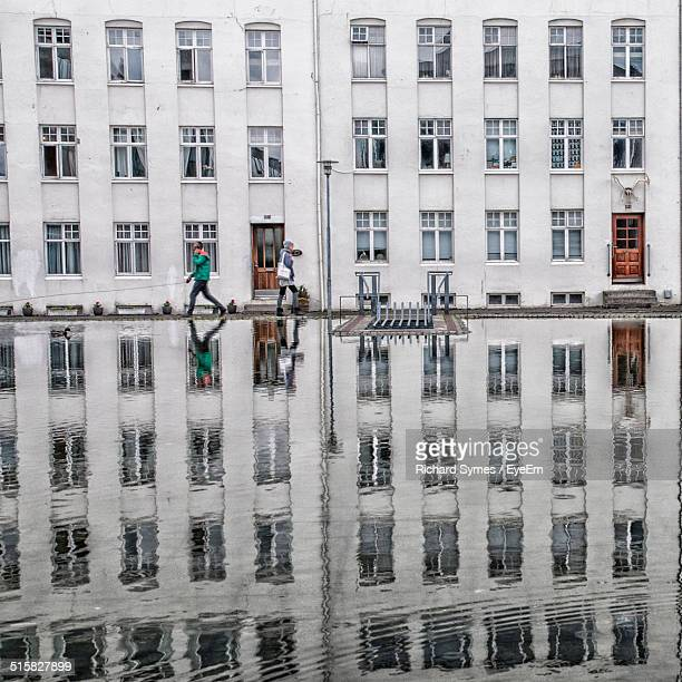 Buildings And People Reflected In Pool
