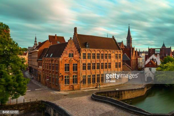 Buildings And Quiet Streets In Bruges City Against Sky