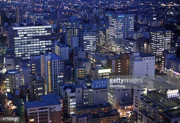Buildings and residential buildings stand illuminated at night in Sendai Miyagi Prefecture Japan on Tuesday March 4 2014 Japan's economic growth is...