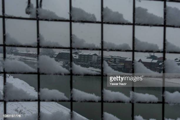 Buildings and residential houses are covered in snow during a fresh snowfall on January 16 2019 in Srinagar the summer capital of Indian administered...