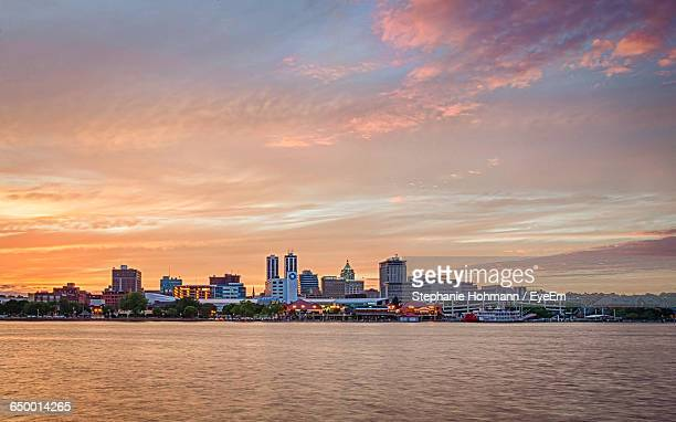 Buildings And River Against Cloudy Sky During Sunset