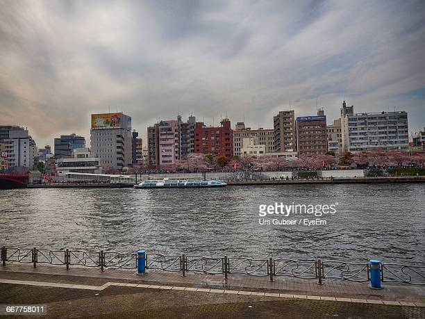Buildings And River Against Cloudy Sky In City