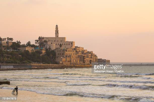 buildings and st peters church by sea against clear sky during sunset - tel aviv stock photos and pictures