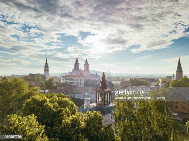 buildings and trees against cloudy sky in city - lithuania stock pictures, royalty-free photos & images