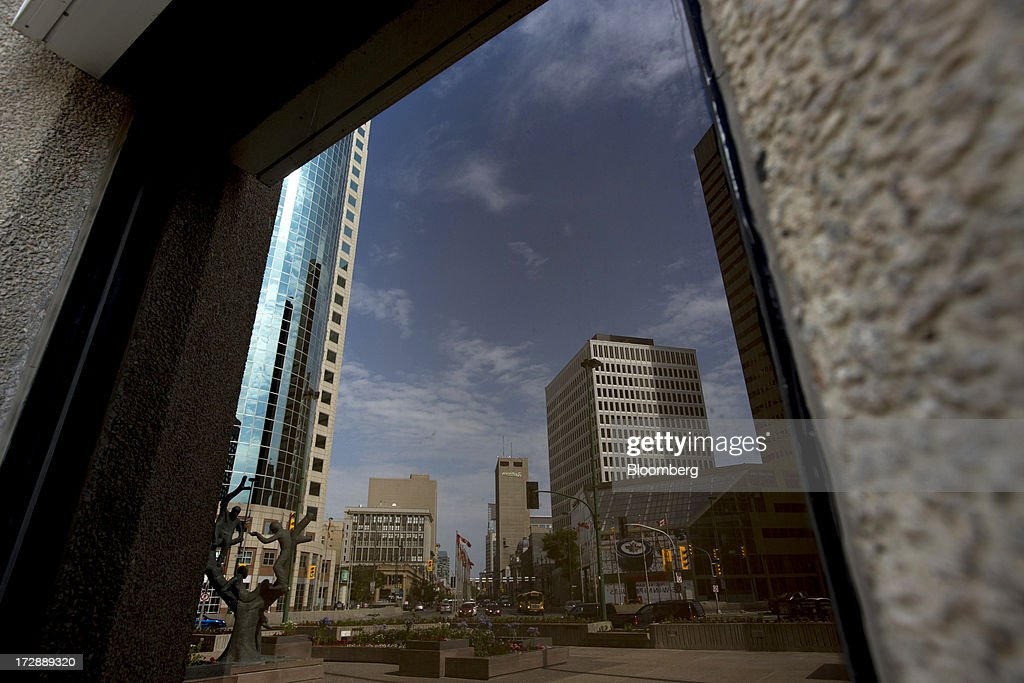 Buildings are reflected in a glass window in Winnipeg, Manitoba, Canada, on Thursday, July 4, 2013. Canada extended the longest streak of merchandise trade deficits in a quarter century in May, with the shortfall narrowing as imports fell faster than exports. Photographer: Brent Lewin/Bloomberg via Getty Images