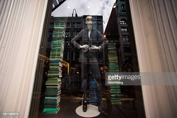 Buildings are reflected in the window display of a Tommy Hilfiger Corp store in the sopping district of Soho in New York US on Saturday Sept 14 2013...