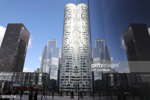 Buildings are reflected in the windows of other buidlings in the La Defense business district in Courbevoie on October 3 2017 / AFP PHOTO / LUDOVIC...