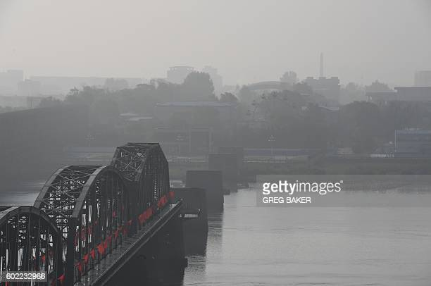 Buildings are seen in the North Korean town of Sinuiju behind the end of the Broken Bridge at Dandong in northeast China on September 11 2016 The...