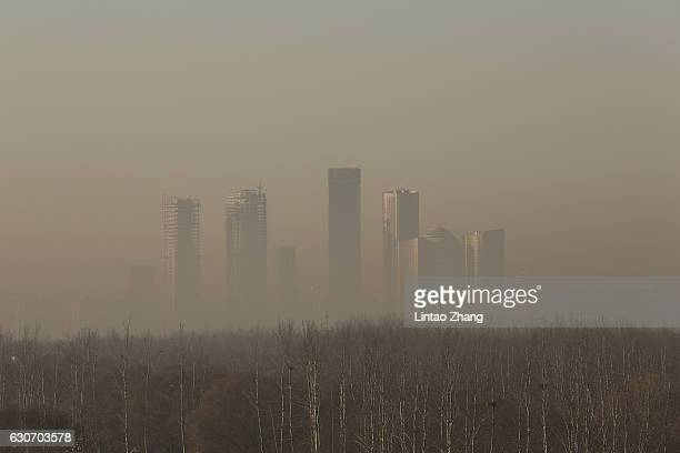 Buildings at central business district are shrouded in heavy smog on December 31 2016 in Beijing China Beijing Meteorological Bureau has issued an...