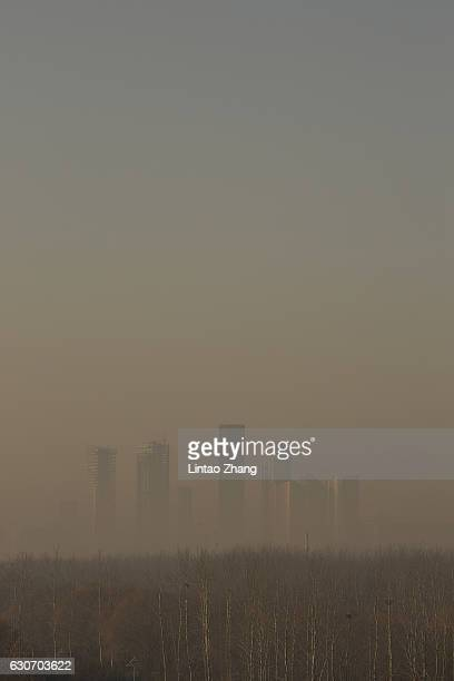 Buildings at central business district are shrouded in heavy smog on December 31, 2016 in Beijing, China. Beijing Meteorological Bureau has issued an...