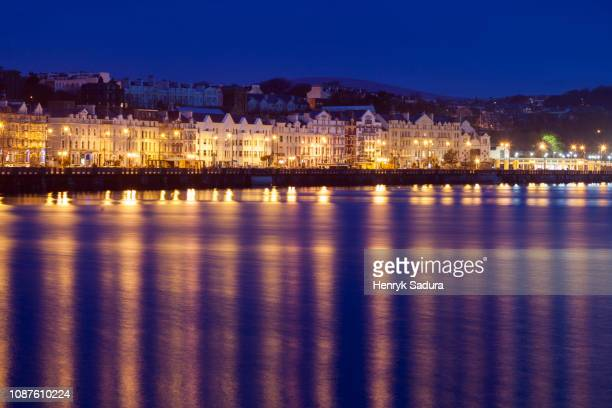 buildings at night along waterfront of douglas, isle of man - isle of man stock pictures, royalty-free photos & images