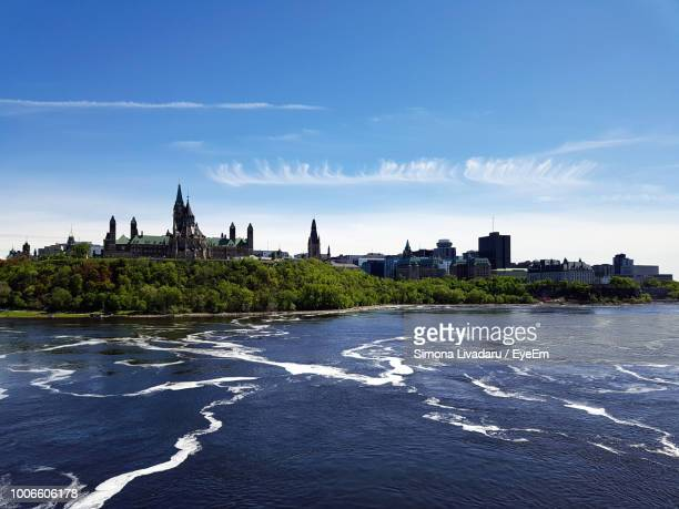 buildings at waterfront against cloudy sky - ottawa stock pictures, royalty-free photos & images