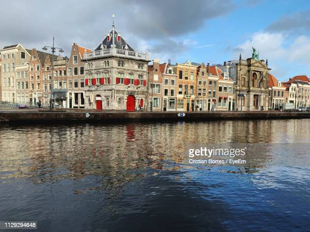 buildings at waterfront against cloudy sky - bortes bildbanksfoton och bilder