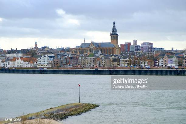 buildings at waterfront against cloudy sky - gelderland stock pictures, royalty-free photos & images