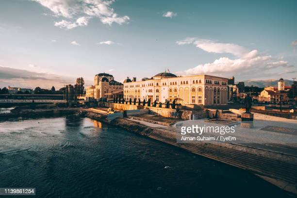 buildings at waterfront against cloudy sky - skopje stock pictures, royalty-free photos & images