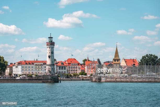 buildings at waterfront against cloudy sky - bodensee stock pictures, royalty-free photos & images