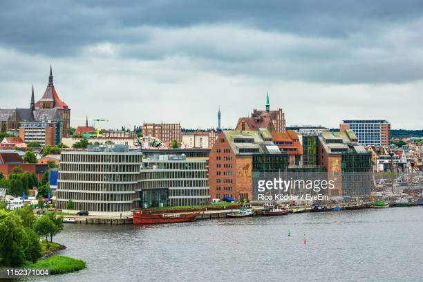 buildings at waterfront against sky - rostock stock pictures, royalty-free photos & images