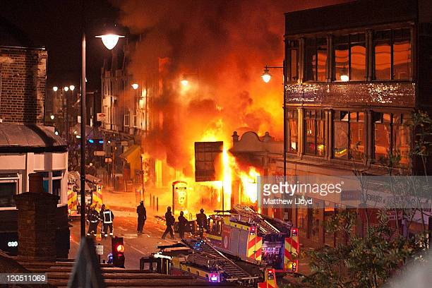 Buildings burn on Tottenham High Road, London after youths protested against the killing of a man by armed police in an attempted arrest, August 6,...