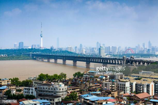 buildings by bridge against sky in city - wuhan stock photos and pictures