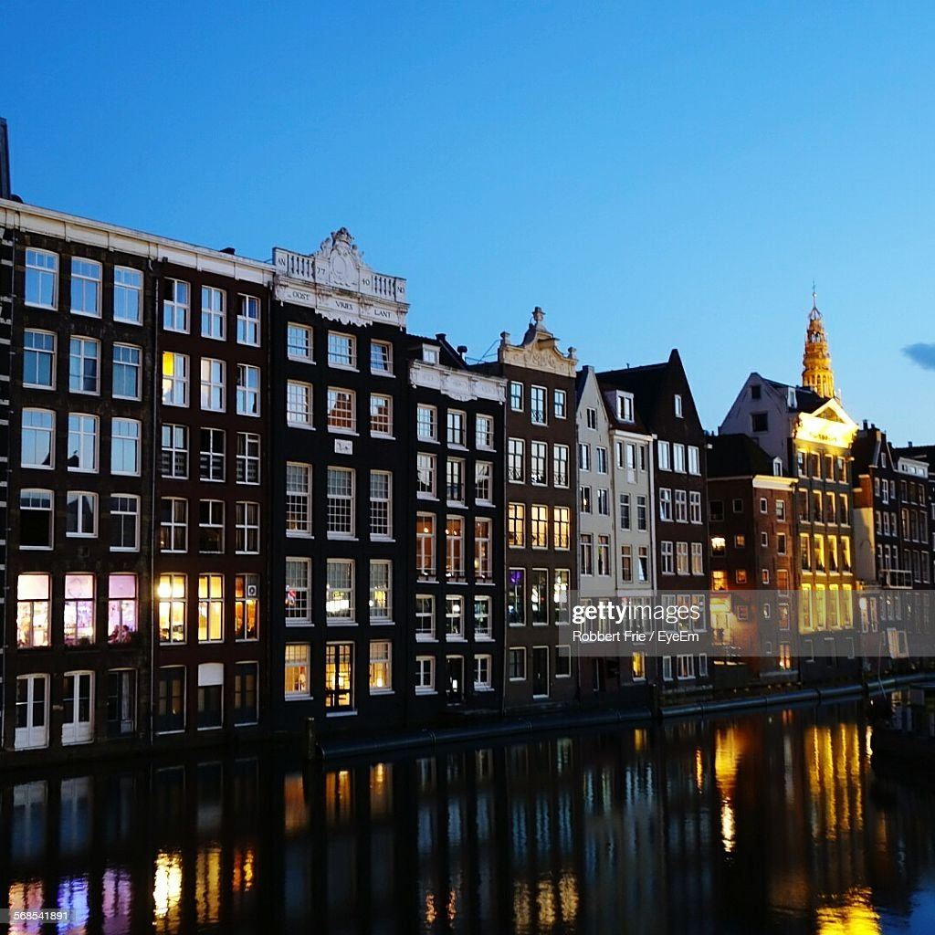Buildings By Canal Against Clear Blue Sky At Dusk : Stock Photo