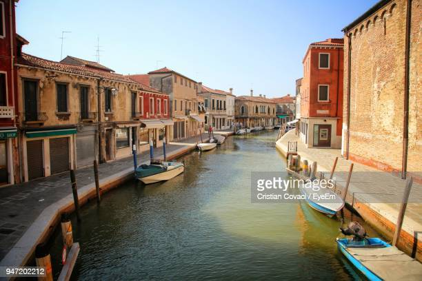buildings by canal against clear sky in city - murano stock pictures, royalty-free photos & images