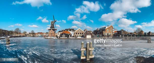 buildings by canal against sky during winter - bortes stock pictures, royalty-free photos & images